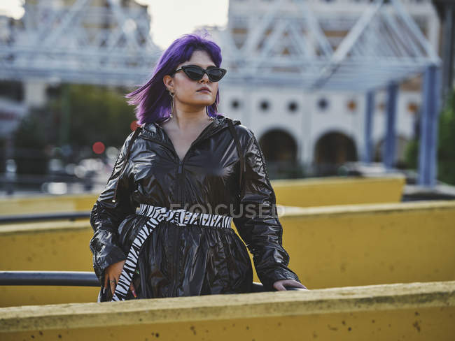 Fashion confident woman with purple hairstyle in shiny black jacket in city in bright daytime — Stock Photo