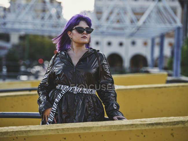 Модная уверенная в себе женщина с фиолетовой прической в блестящем черном пиджаке в ярком дневном городе — стоковое фото