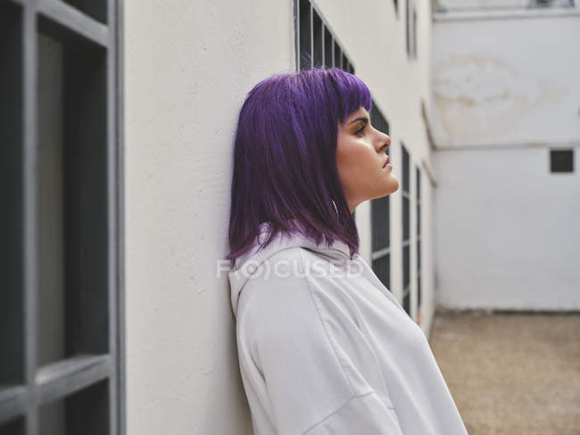Side view of pensive fashion woman with purple hairstyle leaning on white wall and thoughtfully looking away — Stock Photo