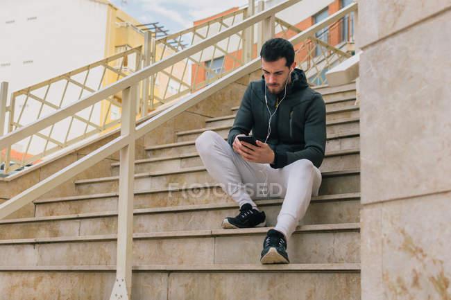 Снизу задумчивый молодой человек в спортивном костюме с наушниками, обменивающимися сообщениями на мобильном телефоне, отдыхающий на лестнице — стоковое фото
