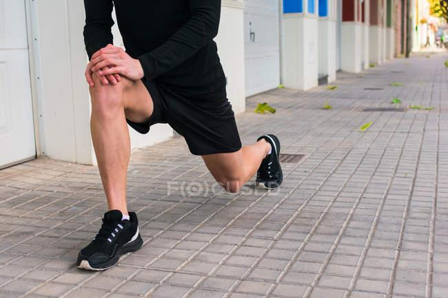 Бездоганний бігун у спортивному одязі зігріває витягнуті ноги, спираючись на коліна, готуючись до бігу на міській вулиці. — стокове фото