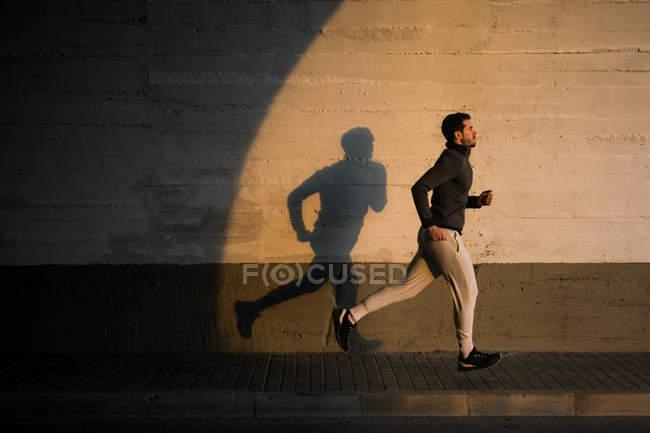 Сторона зору активного хлопця в спортивному одягу тренувальні ноги ковзають по міській вулиці біля бетонної стіни — стокове фото