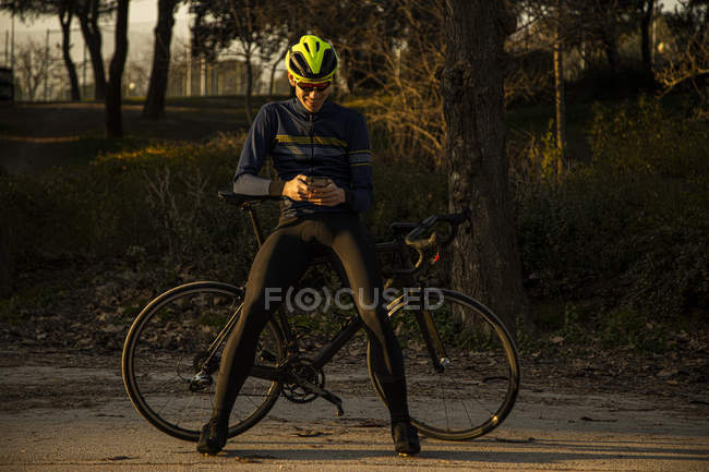 Людина - велогонщик відпочиває, користуючись мобільним телефоном на велодоріжці в парку. — стокове фото