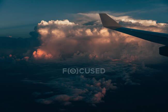 Avión ala entre coloridas nubes grandes y pacíficas y cielo azul al amanecer sobre Cuba - foto de stock