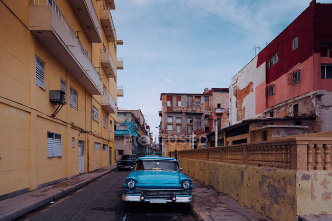 Small street with vintage car in roadside between historical colorful buildings with bars on windows in Cuba — Stock Photo