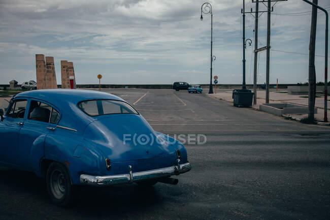 Пересечение асфальтированной дороги с голубым винтажным автомобилем среди современных транспортных средств в центре Кубы — стоковое фото
