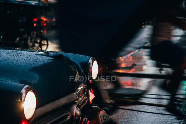 Гуд блакитного вінтажного автомобіля з увімкненим світлом і червоної старої машини в русі на тлі дощової погоди на Кубі. — стокове фото