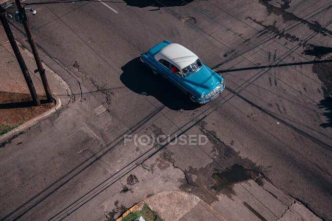Сверху пересечения асфальтовой дороги с красным винтажным автомобилем среди современных транспортных средств в центре Кубы — стоковое фото
