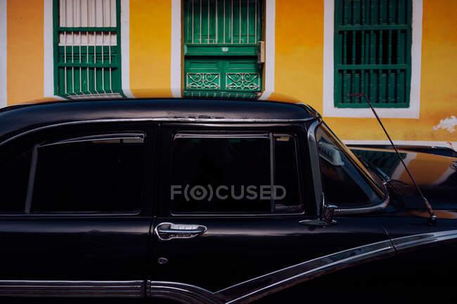 Маленькая улица с черным винтажным автомобилем на обочине между историческими красочными зданиями с решетками на окнах на Кубе — стоковое фото