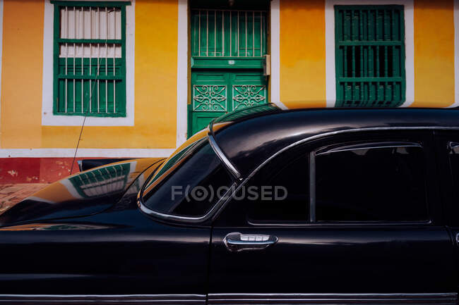 Small street with black vintage car in roadside between historical colorful buildings with bars on windows in Cuba — Stock Photo