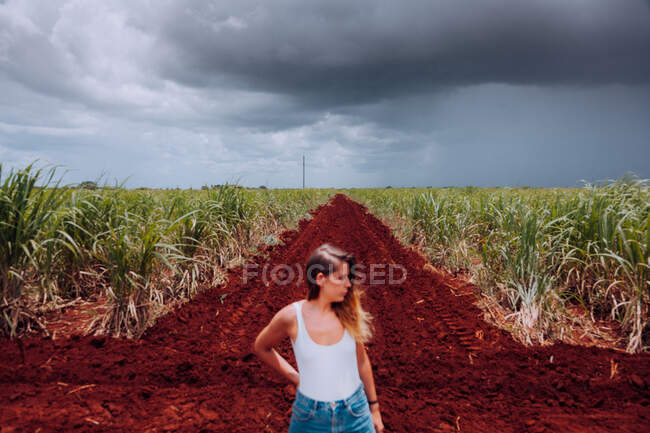 Female traveler in casual wear standing on crossroad with brown soil among green tropical plants under grey cloudy heaven in Cuba — Stock Photo