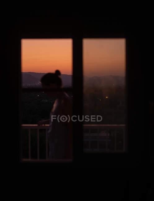 Попереду - молода безлика жінка, що стоїть на балконі з розкішним заходом сонця на розмитому фоні. — стокове фото