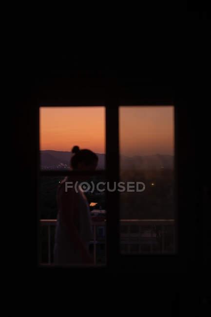 Vista laterale di giovane signora senza volto in piedi in un balcone con magnifico tramonto su sfondo sfocato — Foto stock