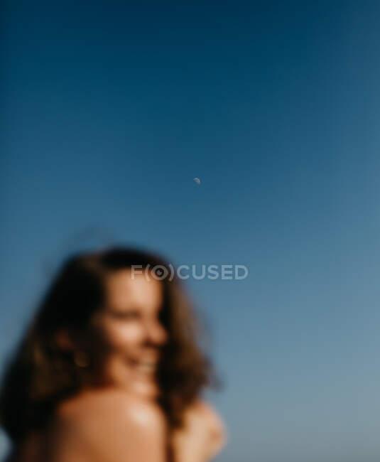 Неразличимая женщина на фоне голубого неба в сумерках — стоковое фото
