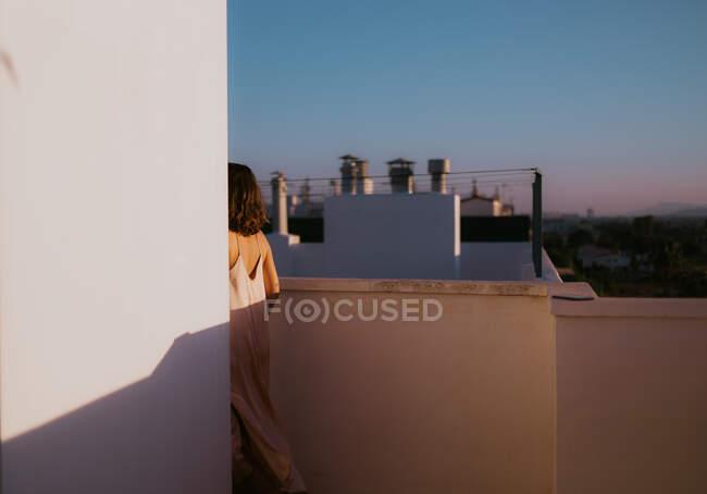 Rückenansicht einer gesichtslosen Frau in hellrosa Seidenkleid, die um die Ecke auf dem gerockten Balkon spaziert — Stockfoto