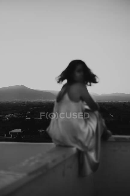На тлі розмитої жінки в стильній шовковій сукні, що сидить на паркані балкона, дивлячись на камеру під час літнього заходу сонця. — стокове фото