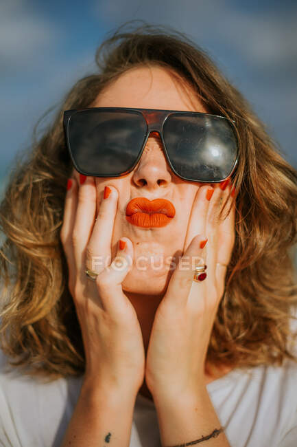 Stylish brown curly haired woman with red lipstick in trendy sunglasses looking at camera while squeezing face in palms — Stock Photo