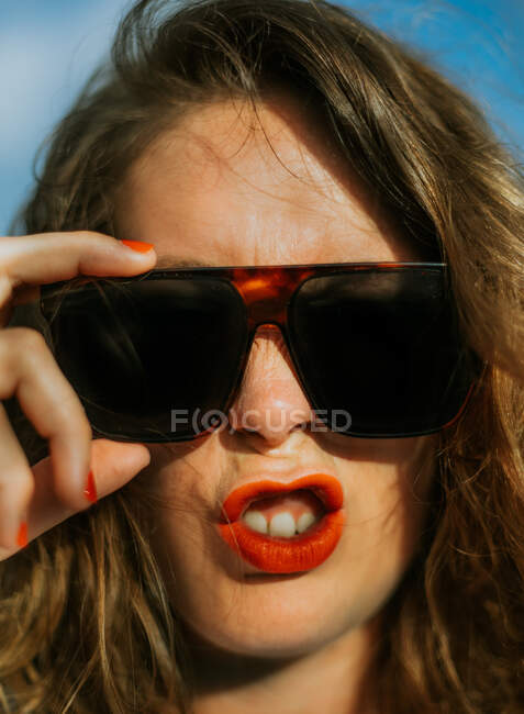 Stylish brown curly haired woman with red lipstick in trendy sunglasses looking at camera while making faces — Stock Photo