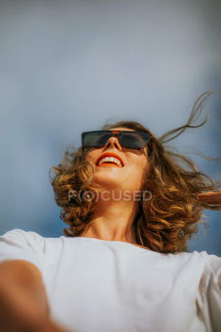 Стильная коричневая кудрявая женщина с красной помадой в триумфальных солнцезащитных очках на фоне голубого неба — стоковое фото