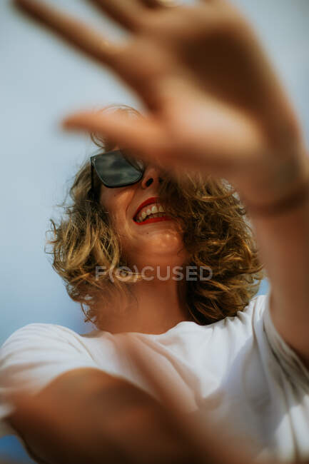 From below stylish brown curly haired woman with red lipstick in trendy sunglasses looking at camera with blue sky on the background — Stock Photo