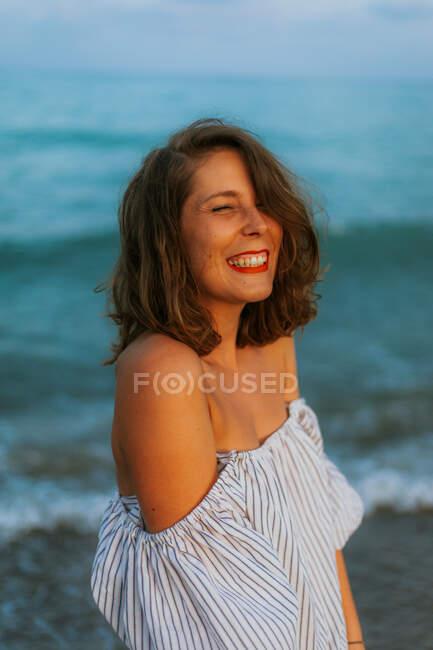Счастливая женщина в легком платье, гуляющая среди маленьких морских волн по пустому побережью в сумерках с закрытыми глазами — стоковое фото