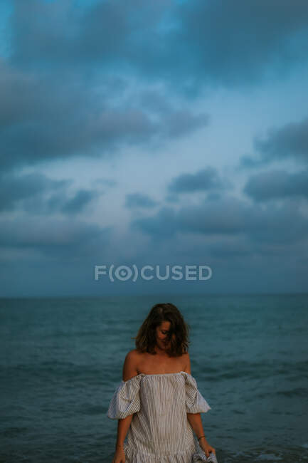 Woman in light dress walking among small sea waves on empty coastline at dusk looking down — Stock Photo