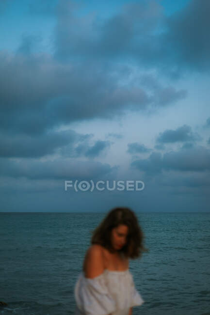 Blurred woman in light dress walking among small sea waves on empty coastline at dusk looking down — Stock Photo