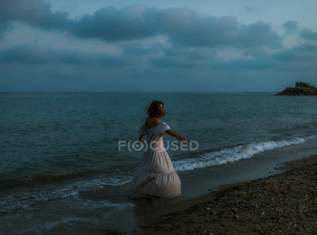 Back view anonymous of barefoot woman traveler in light dress dancing among small sea waves on empty coastline at dusk looking away — Stock Photo