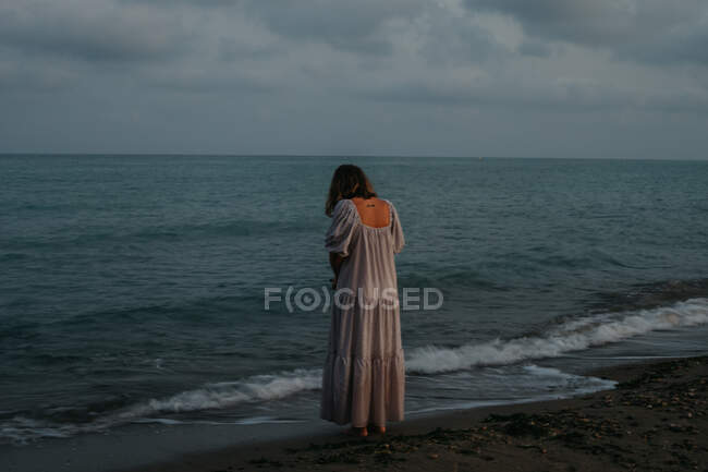 Back view of anonymous barefoot woman traveler in light dress standing among small sea waves on empty coastline at dusk — Stock Photo