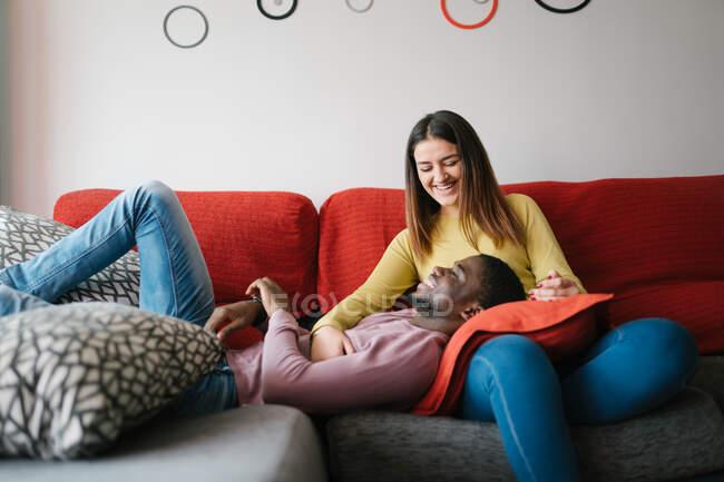 Coppia multirazziale confortevole sdraiato sul divano e smartphone di navigazione — Foto stock