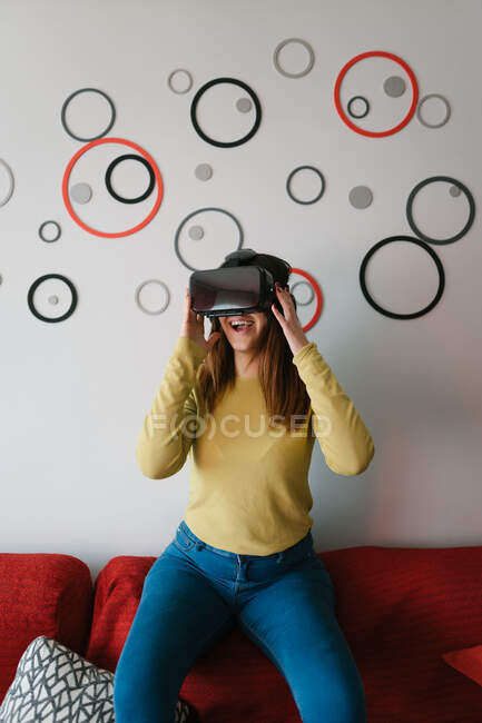 Woman in VR glasses playing on sofa in room — Stock Photo