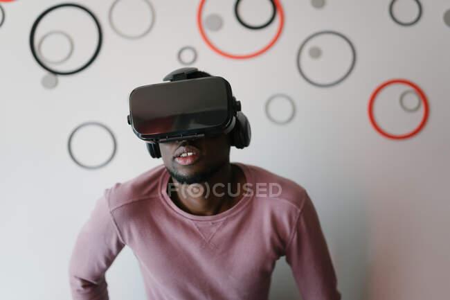 Emocionado hombre negro en gafas VR disfrutando del tiempo en casa - foto de stock