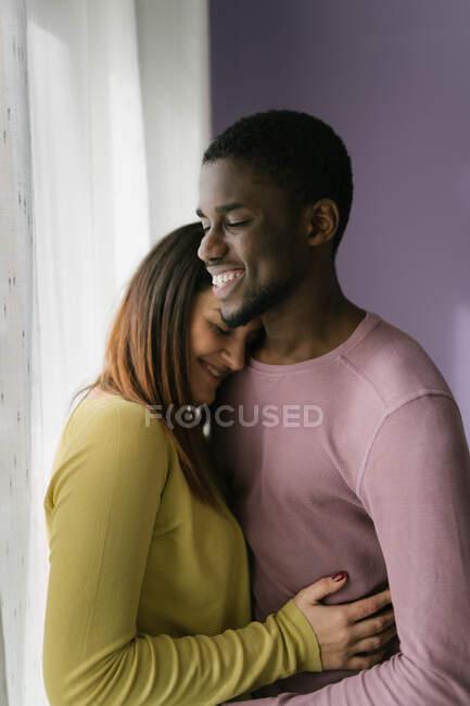 Радостная многонациональная женщина с закрытыми глазами, обнимающая черного мужчину на кухне — стоковое фото