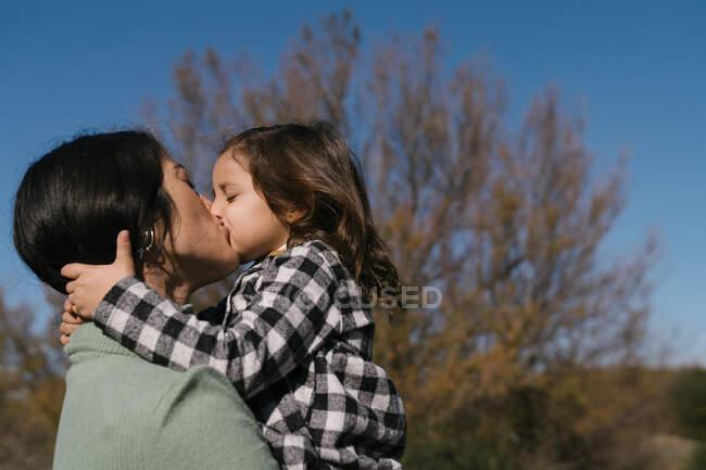 Мать целует и обнимает дочь — стоковое фото