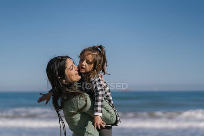 Щаслива етнічна жінка з дитиною на руках на піщаному пляжі. — стокове фото
