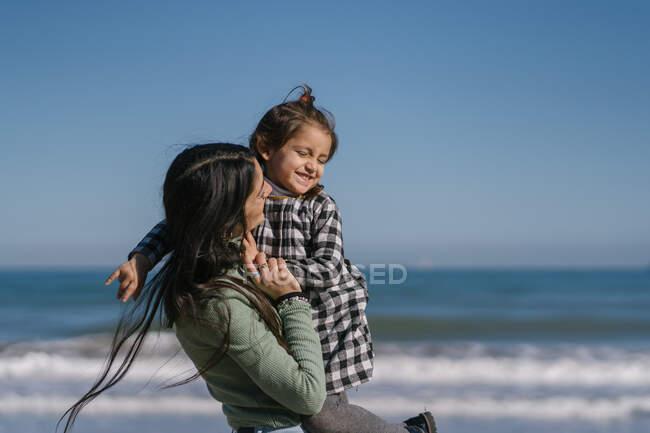 Heureuse femme ethnique avec enfant sur les bras à la plage de sable — Photo de stock