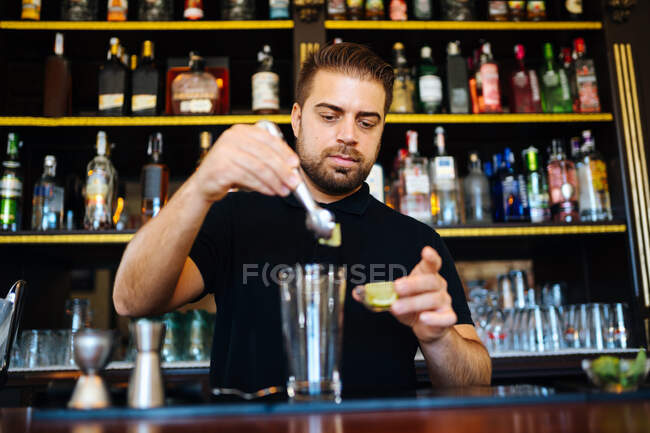 Calm barman pouring alcohol cocktail into jigger and glass on counter making beverage working in bar — Stock Photo