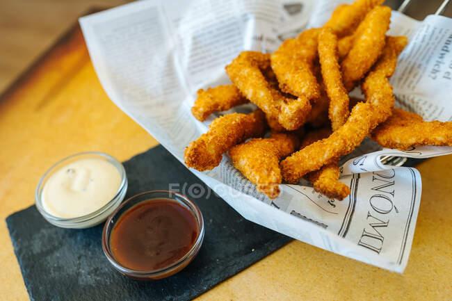 De arriba de los palitos empanados de gallina sobre el papel con la mayonesa y el ketchup sobre la mesa en la cafetería - foto de stock