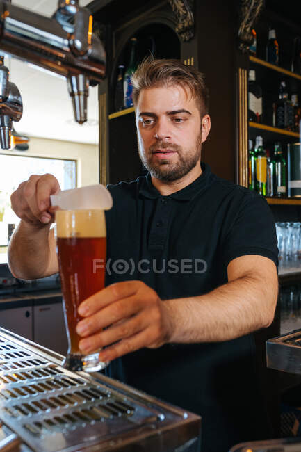 Serious barman in black shirt preparing to serve beer in glass from in bar — Stock Photo