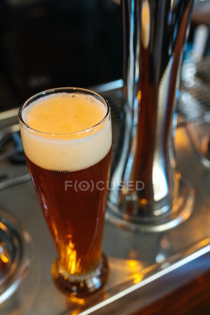 Glass of fresh and cold dark beer with foam on table in pub — Stock Photo