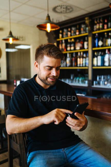 Позитивный молодой человек в повседневной одежде в социальных сетях, сидящий по телефону в собственном баре — стоковое фото