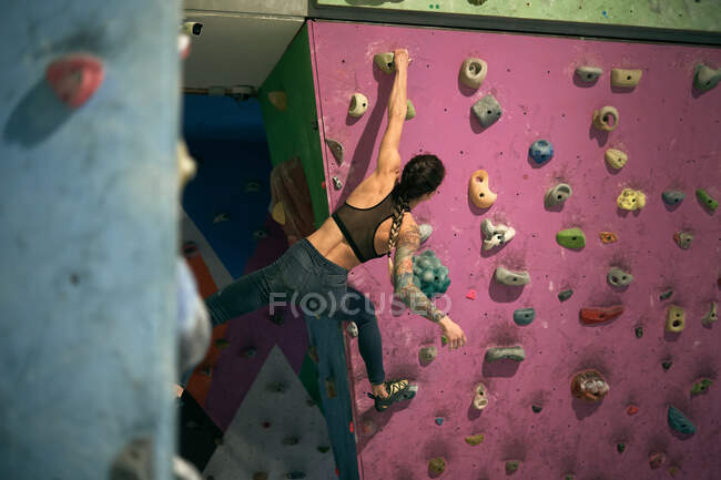 From below back view of unrecognizable athlete tattooed powerful woman climbing on colorful wall with ledges for climbers in room — Stock Photo