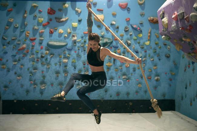 Vista lateral da mulher tatuada entusiasta sorridente segurando corda e pulando no ginásio com parede com bordas para alpinistas — Fotografia de Stock