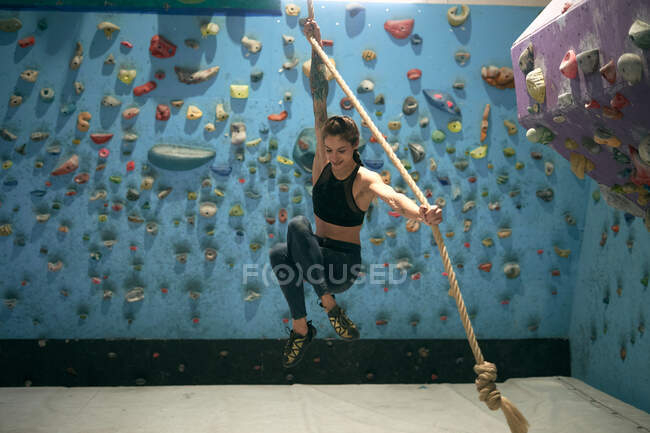 Side view of smiling enthusiastic tattooed woman holding rope and jumping in gym with wall with ledges for climbers — Stock Photo