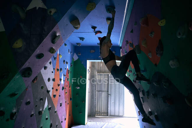 De baixo vista lateral da mulher atleta tatuado mulher poderosa escalada na parede colorida com bordas para alpinistas no quarto — Fotografia de Stock