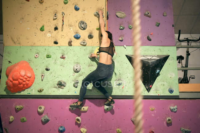 Sporty woman climbing on wall in gym — Stock Photo