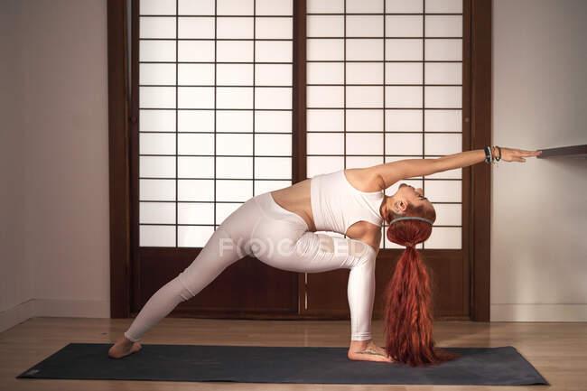 Rückenansicht einer sportlichen jungen Frau, die sich nach rechts lehnt und zu Hause Yoga in Revolved Side Angle Pose auf Matte macht — Stockfoto