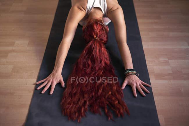 Вид сзади на молодую женщину, расслабляющуюся в детской позе, занимающуюся йогой на коврике дома — стоковое фото