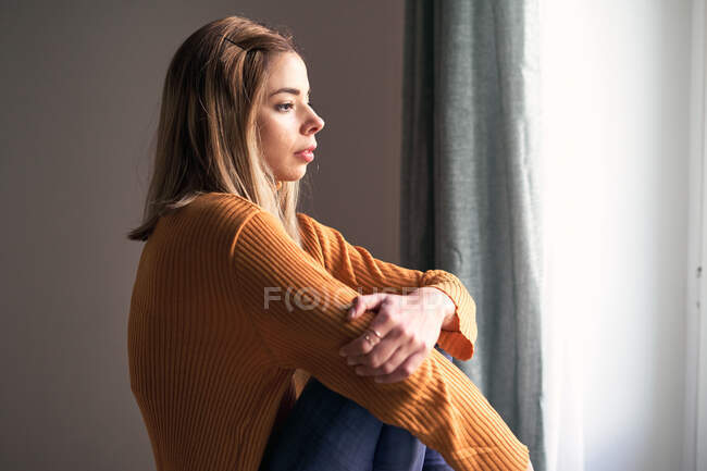 Вид сбоку вдумчивой женщины в повседневной одежде со скрещенными руками, смотрящей в окно, сидящей дома — стоковое фото