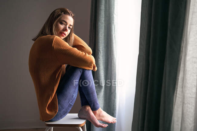 Side view of thoughtful female in casual wear with crossed arms looking at camera sitting at home — Stock Photo